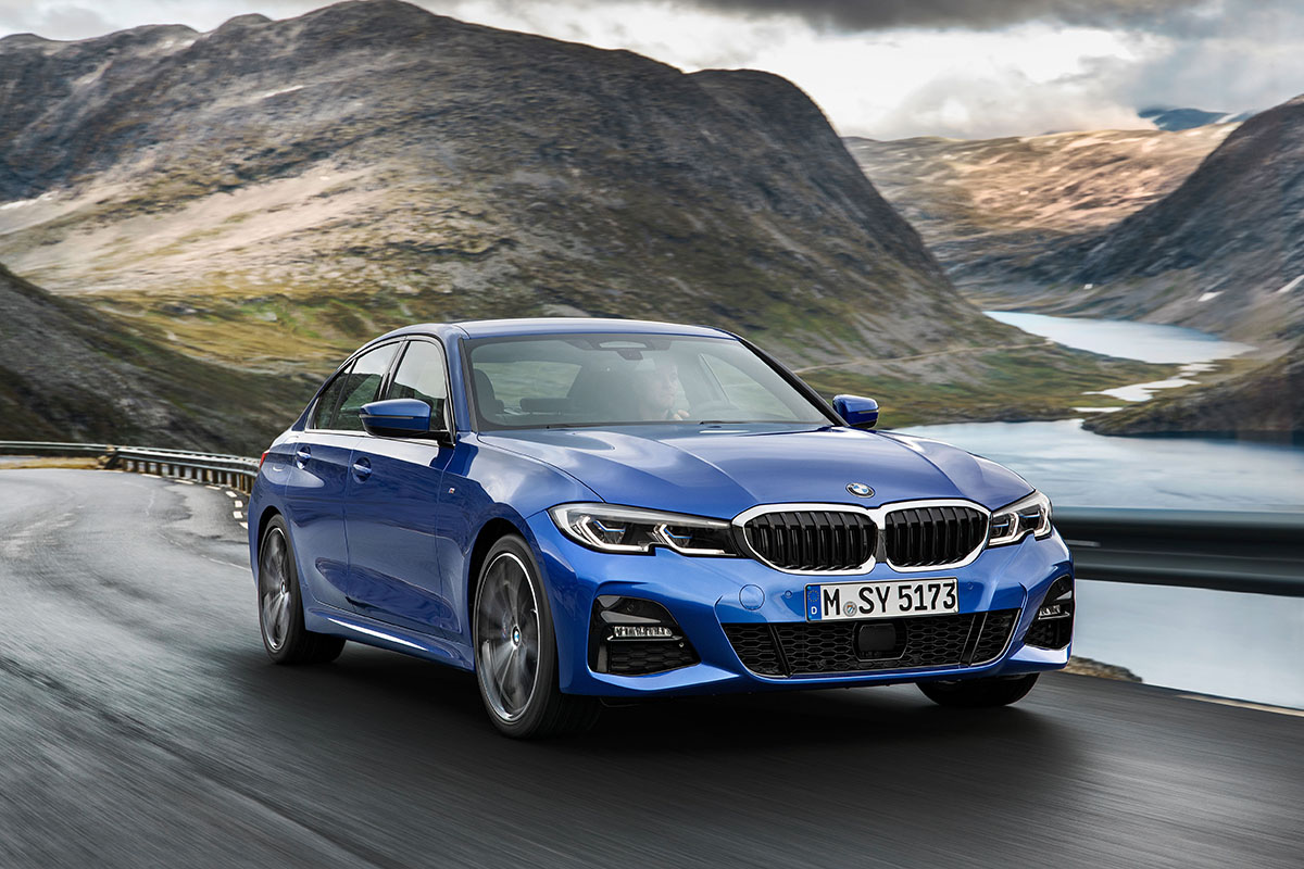 BMW 3 Series (A popular new car) driving down an open road.