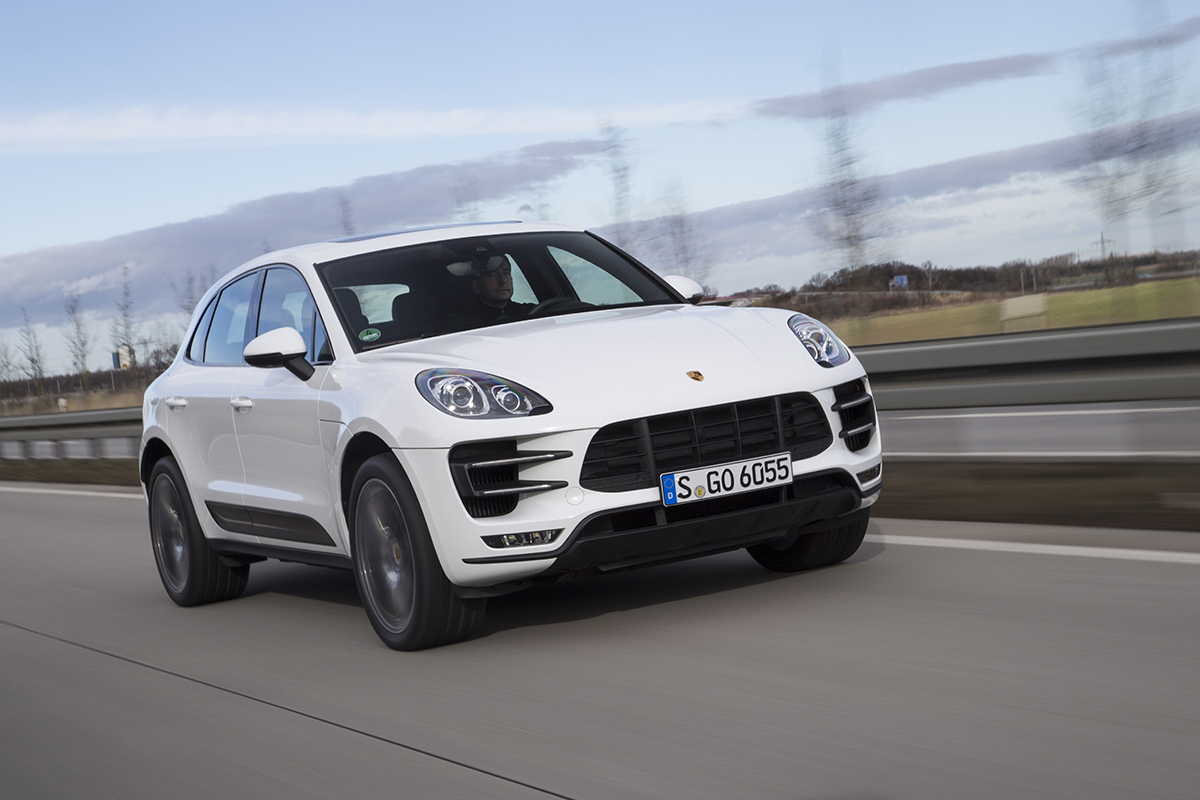 A Porsche Macan Driving Down A Road